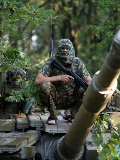 A pro-Russian separatist from the Vostok (East) battalion sits atop a T-64 tank in Donetsk,...