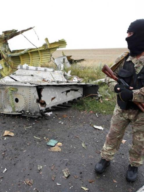 A pro-Russian separatist stands at the crash site of Malaysia Airlines flight MH17, near the...