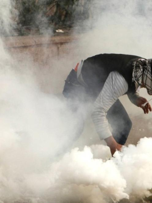 A protester against Egypt's President Mohamed Mursi tries to pick up a tear gas canister fired by...