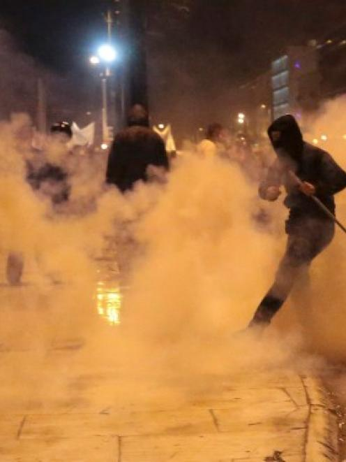 A protester kicks away a gas canister during clashes with riot police in central Athens. REUTERS...