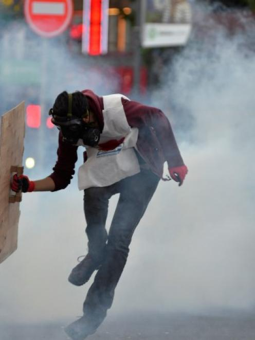 A protester runs away from tear gas fired by riot police during a demonstration in Ankara blaming...