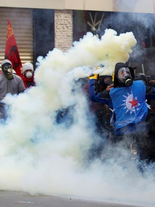A protester throws a flare at riot police during a May Day demonstration in Istanbul. REUTERS...