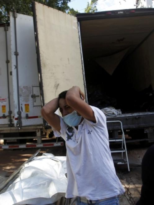 A relative of a prison inmate reacts after seeing body bags containing dead inmates, who died in...