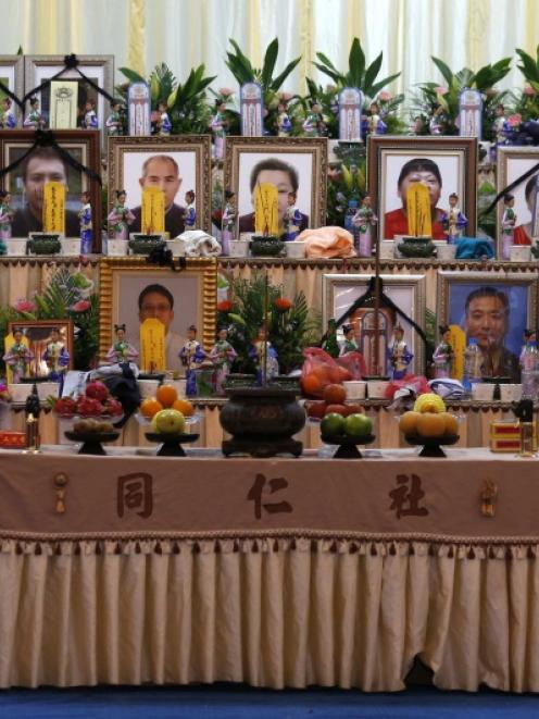 A relative pays her respect in front of portraits of passengers who died in a TransAsia Airways...