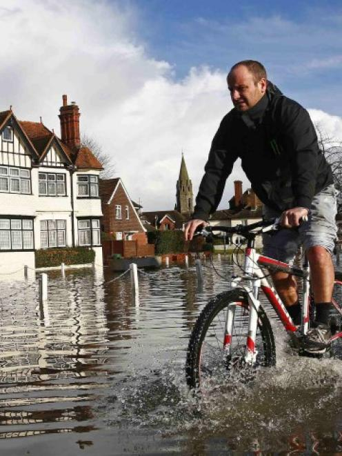 A resident cycles through Thames River floodwater in the village of Datchet. REUTERS/Eddie Keogh