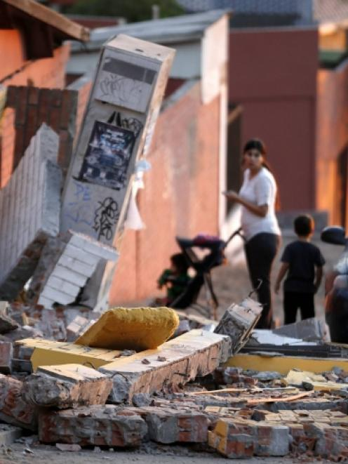 A resident looks at debris around a home after an earthquake and tsunami hit the northern port of...