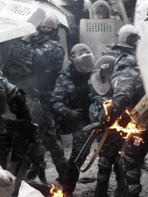 A riot police officer's uniform catches fire during clashes with pro-European protesters in Kiev....