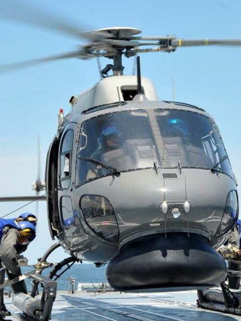 A Royal Malaysian Navy Fennec helicopter crew prepares to depart to aid in the search and rescue...