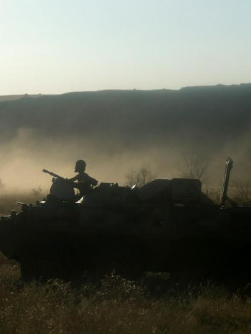 A Russian serviceman rides atop an armoured personnel carrier through a field outside Kamensk...