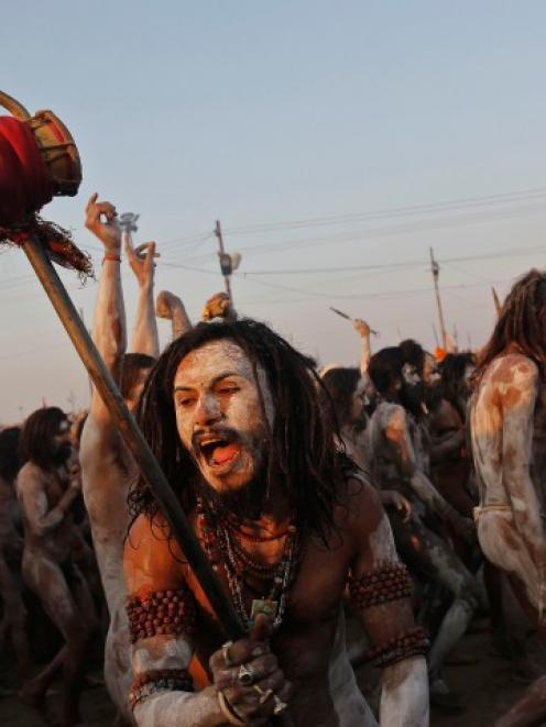 A sadhu, or Hindu holy man, shouts while holding a 'trishul' (trident-shaped weapon} after taking...