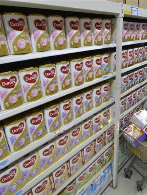 A sales assistant taking down milk powder products which were recalled by Fonterra last year....