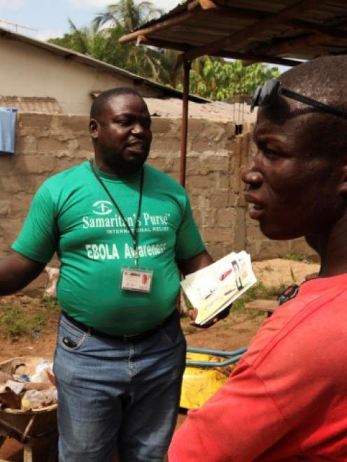 A Samaritan's Purse team member hands out pamphlets to educate the public on the Ebola virus in...