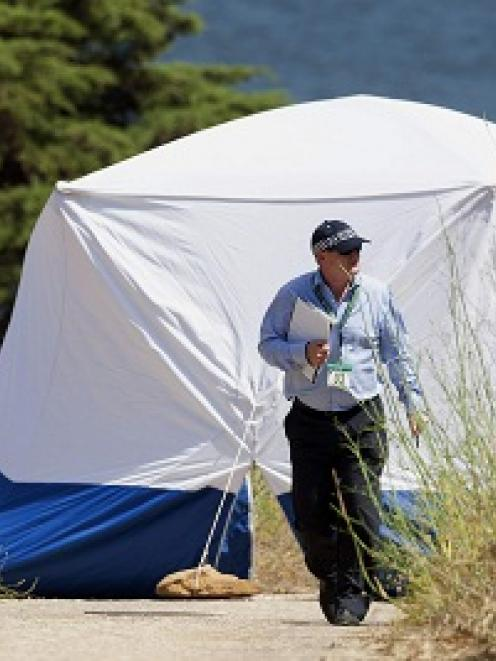 A Scotland Yard detective works on an area in Praia da Luz, near Lagos. REUTERS/Carlos Vidigal