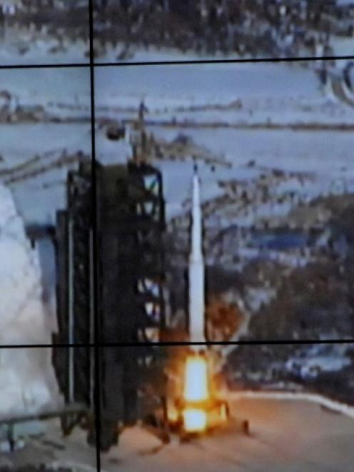 A screen shows the Unha-3 (Milky Way 3) rocket being launched from a launch pad at the North...