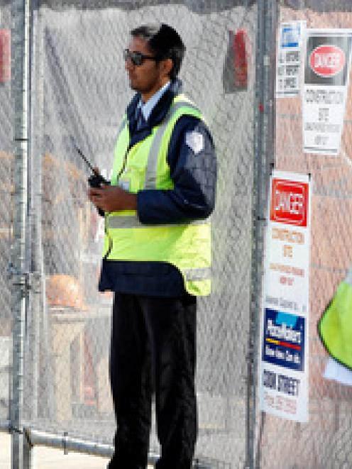 A security guard keeps watch on the closed Mainzeal construction site at Shed 10, Queens Wharf....