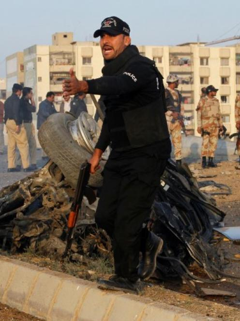 A security officer yells for help at the site of a bomb attack which killed Chaudhry Aslam....