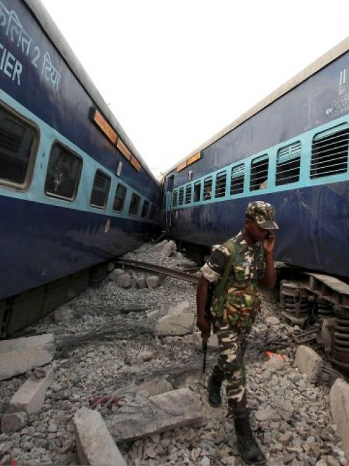 A security staff member speaks on his mobile phone as he walks past the passenger train's damaged...