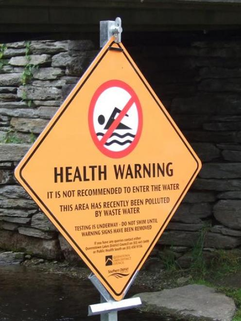 A sign seen yesterday warns people that Horne Creek, at the Village Green, has been polluted by...