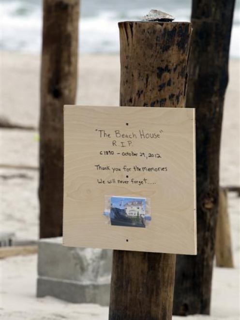 A sign with a photo nailed to one of several pilings, all that remains of a house that once stood...
