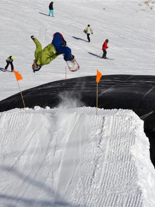 A snowboarder practises jumps and tricks into  a ''super-sized'' air bag fall cushion. ACC is...