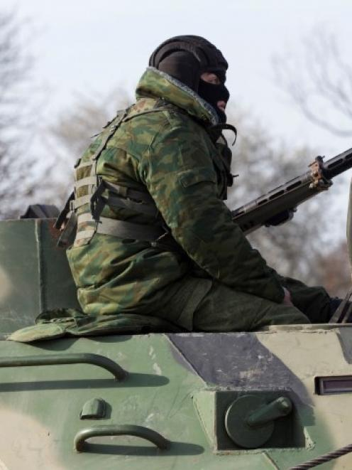 A soldier, believed to be Russian, rides on a military armoured personnel carrier on a road near...