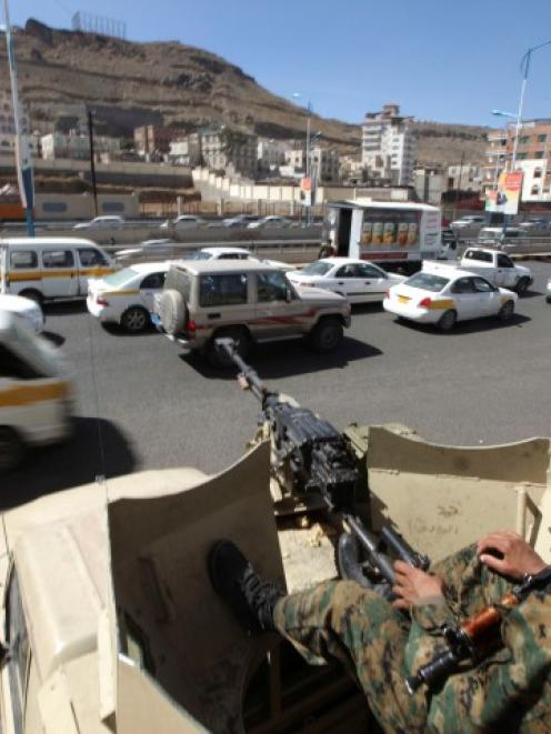 A soldier sits on a military vehicle as others secure a checkpoint on a street in Sanaa, Yemen....