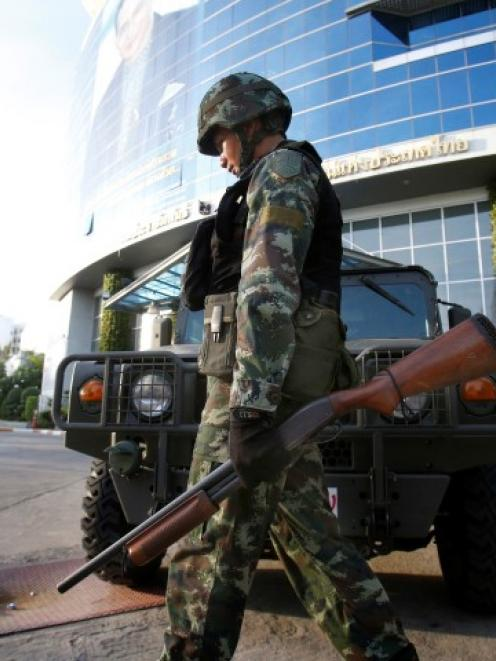 A soldier walks in front of the National Broadcasting Services of Thailand television station in...