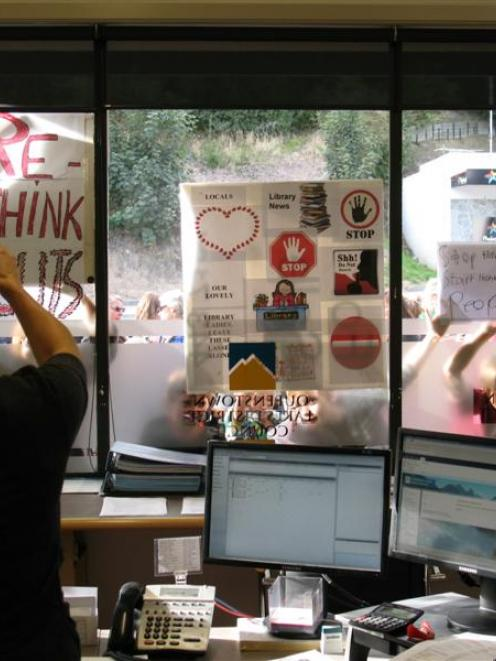 A staff member at the Queenstown Lakes District Council office in Wanaka photographs protesters'...