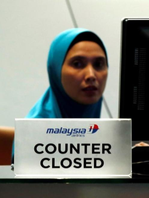 A staff member sits behind a closed Malaysia Airlines desk at Kuala Lumpur International Airport...