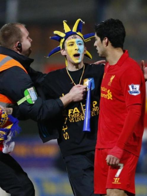A steward prevents a Mansfield Town supporter from reaching Liverpool's Luis Suarez (R) during...