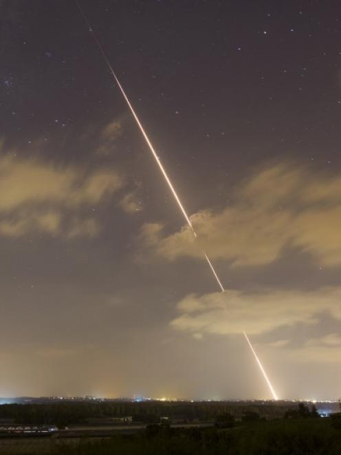 A streak of light is seen as a rocket is launched from the northern Gaza Strip towards Israel....