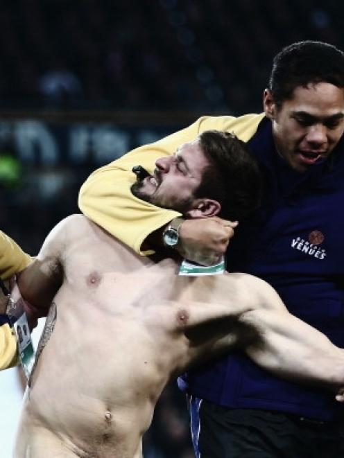 A streaker is taken from the field during the International Test Match between the New Zealand...