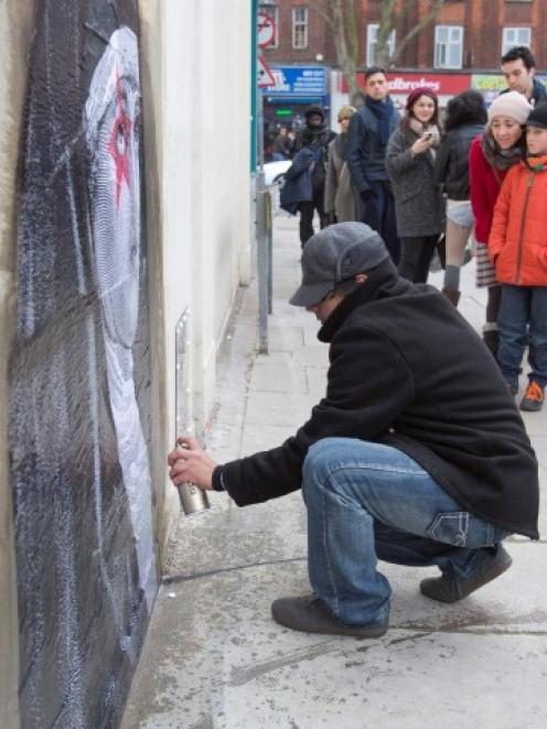 A street artist pastes an image on a London wall from which a section, containing an image...
