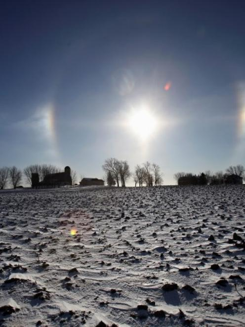 A 'sun dog' atmospheric phenomenon appears over a farm in southern Minnesota. The halo around the...