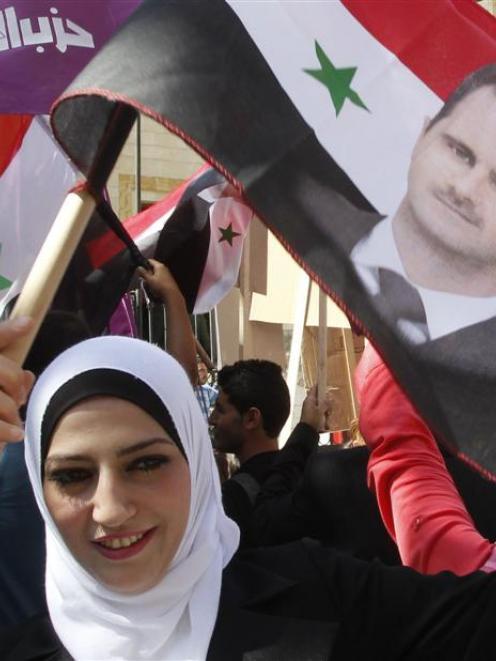 A supporter of Syria's President Bashar al-Assad waves a Syrian national flag depicting Assad's...