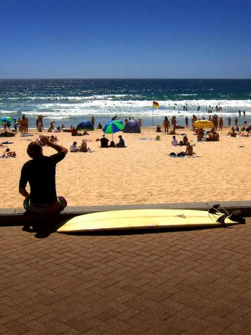 A surfer drinks a coffee as he sits with his surfboard on the footpath above Manly Beach on...