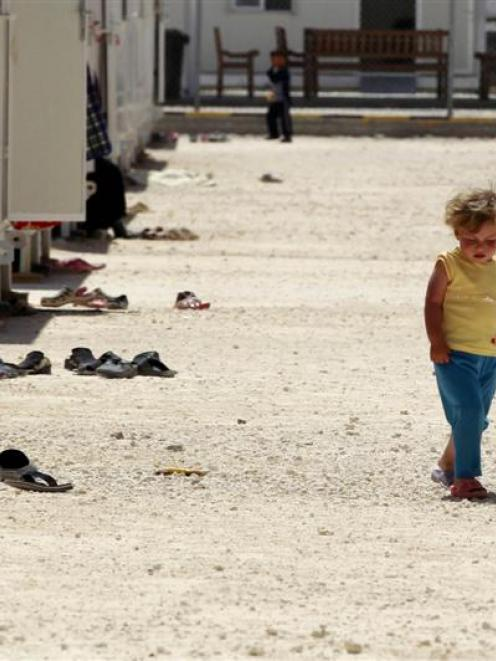 A Syrian refugee girl walks inside the Mrajeeb Al Fhood refugee camp, 20km  east of the city of...