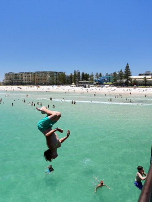 A teengager jumps off the jetty at Glenelg Beach in Adelaide. Five straight days of temperatures...