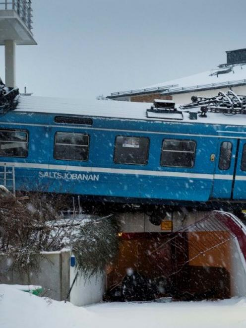 A train that derailed and crashed into a residential building in Saltsjobaden is seen outside...