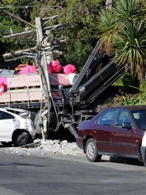 A truck which rolled backwards and damaged four cars, a van and a power pole sits against the...