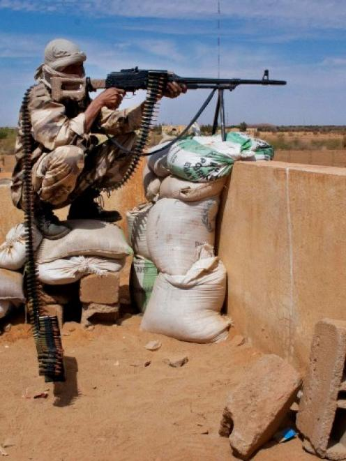 A Tuareg soldier in the Malian army aims his rifle at a checkpoint along a road leading to the...