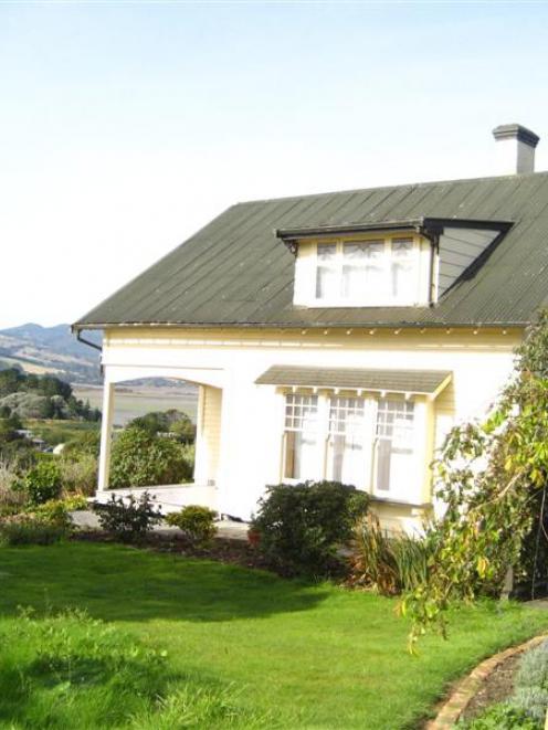 A turn-of-the-century wooden house overlooks Warrington and Blueskin Bay.