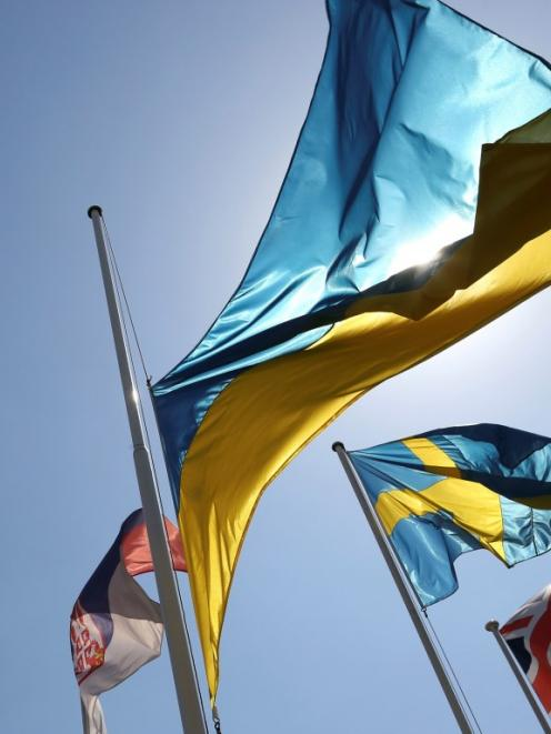 A Ukrainian national flag flies at half-mast near other European flags outside the headquarters...
