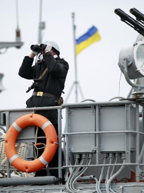 A Ukrainian sailor stands guard on top of a Ukrainian navy ship at the Crimean port of Yevpatorya...