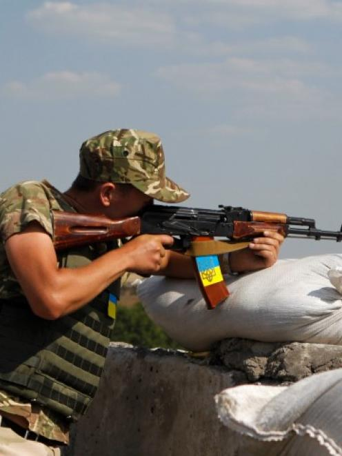 A Ukrainian serviceman test fires his rifle at a checkpoint near the town of Debaltseve, in...