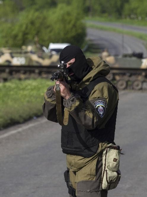 A Ukrainian soldier, with armoured personnel carriers behind him, points his weapon at an...