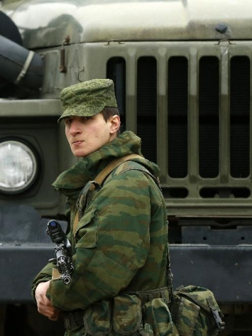 A uniformed man, believed to be a Russian serviceman, stands guard near a Ukrainian military base...