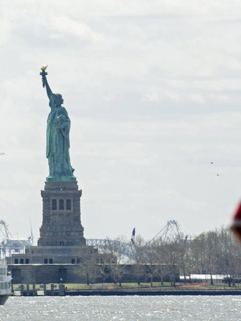 A United States flag flutters in the wind off of a Statue of Liberty Island ferry boat in lower...