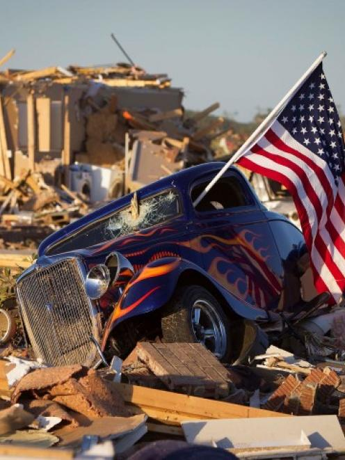 A US flag sticks out the window of a damaged hot rod in a suburban area after a tornado near...