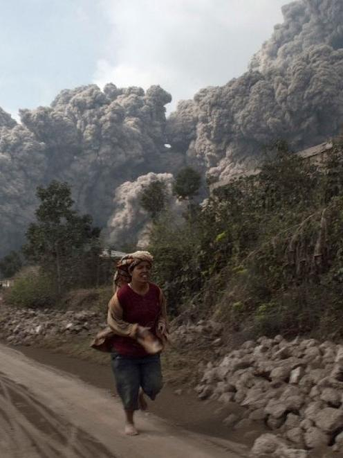 A villager runs as Mount Sinabung erupt at Sigarang-Garang village in Karo district, Indonesia's...